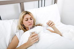 Woman suffering from cold holding water and tablet in bed Royalty Free Stock Image