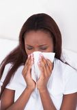 Woman suffering from cold at home. Young woman blowing nose while suffering from cold at home Stock Photo