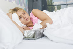 Woman suffering from cold lying with tissue box on bed Royalty Free Stock Images