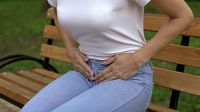 Woman suffering from cystitis, touching abdomen and feeling pain, healthcare royalty free stock photography