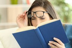 Woman suffering eyestrain reading a book. Woman suffering eyestrain trying to read a book at home Stock Photography