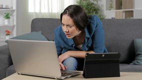 Woman suffering eyestrain using multiple devices. Sitting on a couch at home stock footage
