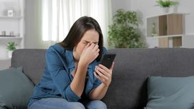 Woman suffering eyestrain using smart phone. Sitting on a couch at home stock video footage