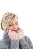 Woman suffering with freezing temperatures. Cold woman pulling the collar of her warm jacket high around her cheeks suffering with freezing winter temperatures royalty free stock photography