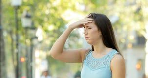 Woman suffering head ache in the street. Woman suffering head ache walking and complaining in the street stock footage