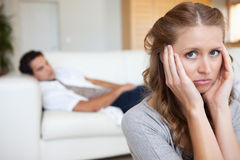 Woman suffering from headache with man on the sofa behind her Royalty Free Stock Image