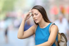 Woman suffering headache outdoor in the street stock photo