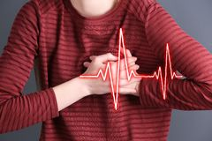 Woman suffering from heart attack on color background. Closeup stock photos