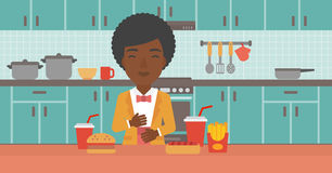 Woman suffering from heartburn. An african-american woman standing in the kitchen in front of table full of junk food and suffering from heartburn vector flat Stock Photography