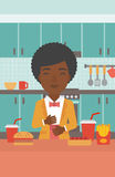 Woman suffering from heartburn. An african-american woman standing in the kitchen in front of table full of junk food and suffering from heartburn vector flat Royalty Free Stock Photo