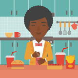 Woman suffering from heartburn. An african-american woman standing in the kitchen in front of table full of junk food and suffering from heartburn vector flat Stock Image