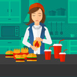 Woman suffering from heartburn. A woman standing in the kitchen in front of table full of junk food and suffering from heartburn vector flat design illustration Stock Photography
