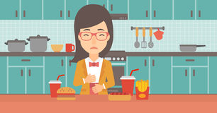 Woman suffering from heartburn. A woman standing in the kitchen in front of table full of junk food and suffering from heartburn vector flat design illustration Royalty Free Stock Images