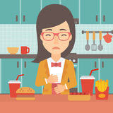 Woman suffering from heartburn. A woman standing in the kitchen in front of table full of junk food and suffering from heartburn vector flat design illustration Royalty Free Stock Photos