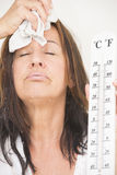 Woman suffering from heat and sweat. Portrait beautiful mature woman suffering from heat, high temperature, fever, with drops of sweat runing down face and Royalty Free Stock Photo