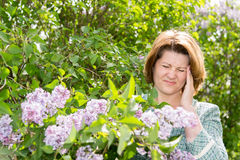 Woman suffering from migraine about blooming lilac Stock Photos