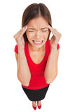 Migraine headache woman suffering. Woman suffering from a migraine headache rubbing her temples with her fingers and grimacing in pain, high angle full length Stock Photo
