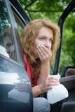 Woman suffering from motion sickness. In a car and holding sick bag royalty free stock images