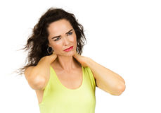 Woman suffering from neck pain. A woman suffering from neck ache is rubbing her neck. Isolated woman stock photo