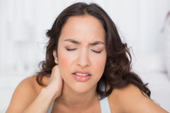 Woman suffering from neck pain with eyes closed Stock Photos