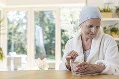 Woman suffering from ovarian cancer wearing bathrobe and headscarf taking pills at home. Senior woman suffering from ovarian cancer wearing bathrobe and stock image