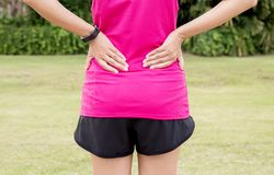 Woman suffering from pain in back injury after sport exercise running jogging and workout royalty free stock image