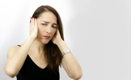 Woman suffering pain, headache. Woman with hands on her ears and suffering expression isolated over white Royalty Free Stock Image