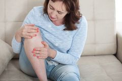 Woman suffering from pain in knee, close up royalty free stock photos