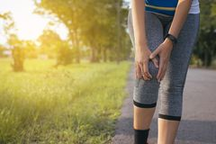 Woman suffering from pain in legs and knee injury after running jogging with workout. In park Stock Photography