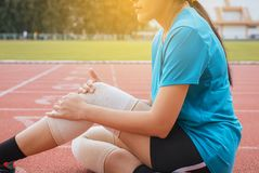 Woman suffering from pain in legs with knee injury after sport exercise running jogging and workout stock images