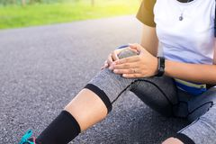 Woman suffering from pain in legs,knee injury after sport exercise running jogging and workout. Outdoor Royalty Free Stock Image