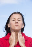 Woman suffering from pain in throat. Portrait attractive mature woman stressed and suffering from painful throat ache, closed eyes, concentrated, with hands on Royalty Free Stock Photography