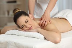 Woman suffering receiving a massage Stock Images