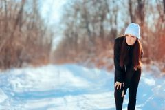 Woman Suffering Running Injury Leg Accident in Winter Training Session. Hurt girl in pain for exercising without stretching properly before Royalty Free Stock Image