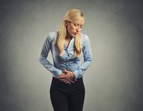 Woman suffering from severe pain in her tummy. Isolated on gray wall background royalty free stock photos