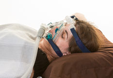 Woman suffering from sleep apnea wearing mask. Hispanic middle age lady suffering from sleep apnea and wearing the cpap mask to relieve her condition or disorder Royalty Free Stock Photos