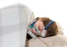 Woman suffering from sleep apnea wearing mask. Hispanic middle age lady suffering from sleep apnea and wearing the cpap mask to relieve her condition or disorder Royalty Free Stock Image