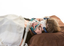 Woman suffering from sleep apnea wearing mask Royalty Free Stock Photography