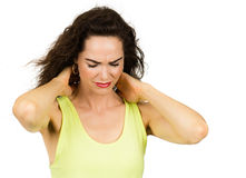 Woman suffering from stiff sore neck. A woman is rubbing her stiff and sore neck. Isolated on white stock image