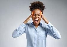 Woman suffering from stress or a headache grimacing in pain. Photo of african american woman in blue shirt on gray background. Medical concept stock image