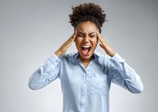 Woman suffering from stress or a headache grimacing in pain. Photo of african american woman in blue shirt on gray background. Medical concept royalty free stock photography