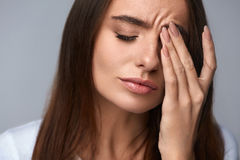 Woman Suffering From Strong Pain, Having Headache, Touching Face. Pain. Tired Exhausted Stressed Woman Suffering From Strong Eye Pain. Portrait Of Beautiful Royalty Free Stock Image