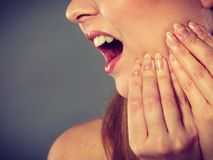 Woman suffering from tooth pain. Dental care and toothache. Young woman achy girl suffering from terrible tooth pain, touching pressing her cheek by hand palm stock photo