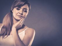Woman suffering from tooth pain. Dental care and toothache. Young woman achy girl suffering from terrible tooth pain, touching pressing her cheek by hand palm royalty free stock photos
