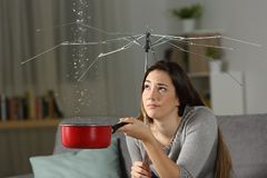 Woman suffering water leaks with a bad insurance concept. Woman suffering water leaks at home with a broken umbrella. Bad insurance concept Royalty Free Stock Photo