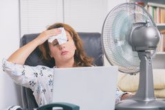 Woman suffers from heat in the office or at home royalty free stock image