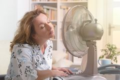 Woman suffers from heat in the office or at home royalty free stock photography