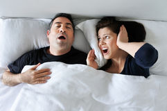 Woman suffers from her partner snoring in bed. Woman (age 30-40) suffers from her partner (age 35 - 45) snoring in bed. Couple lifestyle and people health care Stock Images