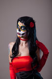 Woman with sugar skull make-up. Wearing red dress, the Day of the Dead royalty free stock photography