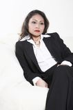 A woman in a suit. Asian. The portrait of a woman which is dressed in a suit and she  sits on a sofa Royalty Free Stock Photography
